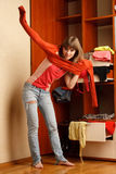 Young woman puts on  orange sweater Royalty Free Stock Images