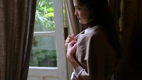 A young woman puts on a robe. Dim lighting in the room. Relax and comfort.  stock video footage