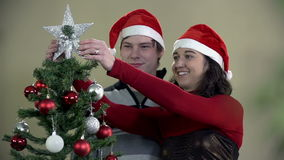 Young woman puts shiny star on Christmas tree and hugs boyfriend. Young romantic couple decorating Christmas tree by a fireplace with red and silver ornaments stock footage