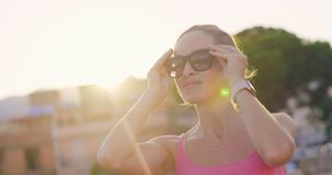 Young woman puts on sunglasses before walking stock video footage