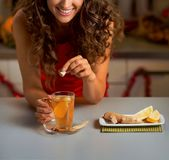 Young woman putting brown sugar cube into ginger tea Royalty Free Stock Image