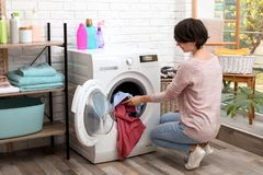 Young woman putting clothes into washing machine stock photos