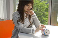 Young woman putting coin in piggy bank Royalty Free Stock Image