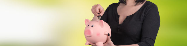 Young woman putting coin in piggy bank Royalty Free Stock Photography