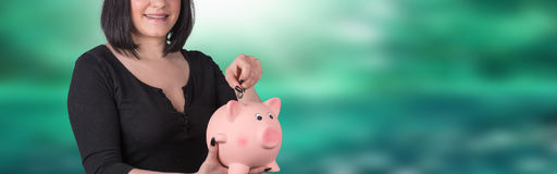 Young woman putting coin in piggy bank Royalty Free Stock Images