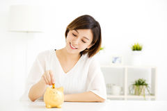 Young Woman Putting Coin In Piggy Bank Stock Photo