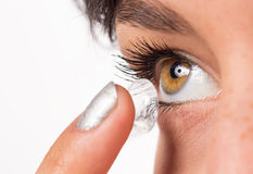 Young woman putting contact lens in her eye. Royalty Free Stock Images
