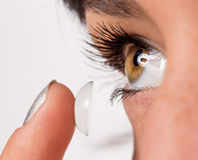 Young woman putting contact lens in her eye. Royalty Free Stock Photography