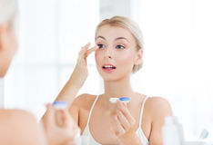 Young woman putting on contact lenses at bathroom Royalty Free Stock Images