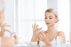 Young woman putting on contact lenses at bathroom Stock Photo