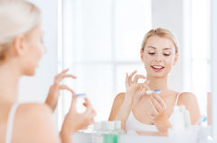 Young woman putting on contact lenses at bathroom Royalty Free Stock Photos