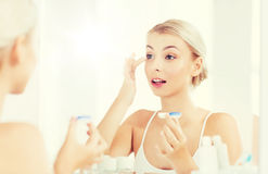 Young woman putting on contact lenses at bathroom. Beauty, vision, eyesight, ophthalmology and people concept - young woman putting on contact lenses at mirror stock photos