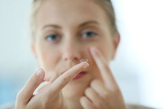 Young woman putting in contact lenses Stock Photo