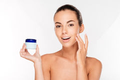 Young woman putting cream on her face Stock Image