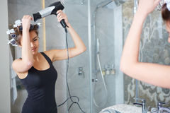 Young woman putting curlers in her hair, bathroom Stock Images