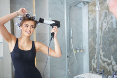 Young woman putting curlers in her hair, bathroom Stock Image