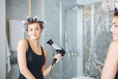 Young woman putting curlers in her hair, bathroom Stock Photos
