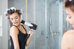 Young woman putting curlers in her hair, bathroom Stock Photo