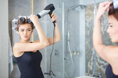 Young woman putting curlers in her hair, bathroom Royalty Free Stock Image