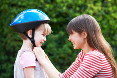 Young Woman Putting Cycle Helmet Onto Girl Royalty Free Stock Images