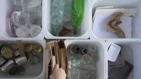 Young woman is putting different garbage in containers for recycling at home interior. Spbd