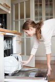 Young woman putting dishes in the dishwasher Royalty Free Stock Image