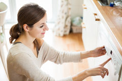 Young woman putting dishes in the dishwasher Royalty Free Stock Images
