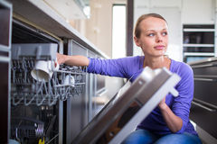 Young woman putting dishes in the dishwasher Stock Photo