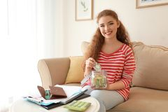 Young woman putting dollar banknote into glass jar indoors. Money savings concept stock photography