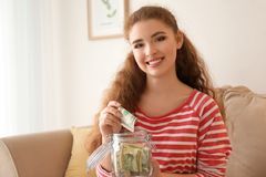 Young woman putting dollar banknote into glass jar indoors. Money savings concept stock images