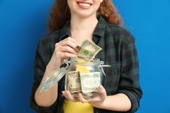 Young woman putting dollar banknote into glass jar with money on color background. Money savings concept royalty free stock image