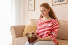 Young woman putting dollar banknote into wallet indoors. Money savings concept royalty free stock images