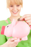 Young woman putting euro coin in piggy bank Stock Image