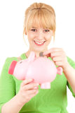 Young woman putting euro coin into piggy bank Royalty Free Stock Photography