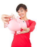 Young woman putting euro in piggybank Royalty Free Stock Images