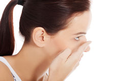 Young woman is putting eye lens. Royalty Free Stock Image