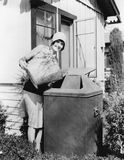 Young woman putting garbage into a garbage can Royalty Free Stock Photos
