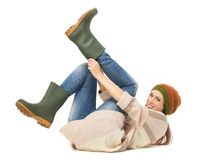 Young Woman Putting on Gardening Boots. Young woman on the floor smiling and putting on gardening boots. Isolated on white background Royalty Free Stock Photos
