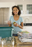 Young woman putting glass bottle and can into recycling bin in kitchen, smiling, portrait. Young women putting glass bottle and can into recycling bin in kitchen Royalty Free Stock Photography