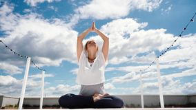 Young woman is putting hands in namaste posture sitting in lotus position. And breathing relaxing. Girl meditates in background of white clouds and blue sky stock video
