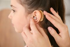 Young woman putting hearing aid in daughter`s ear, closeup. Young woman putting hearing aid in daughter`s ear indoors, closeup royalty free stock images