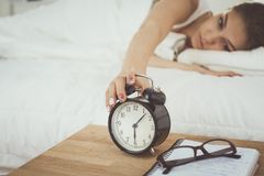 A young woman putting her alarm clock off in the morning. Stock Photography