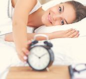 Young woman putting her alarm clock off in the morning Stock Photography