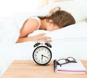 A young woman putting her alarm clock off in the morning.  Stock Photo