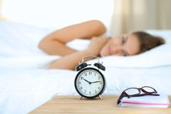 A young woman putting her alarm clock off in the morning.  Royalty Free Stock Images