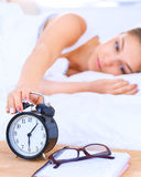 A young woman putting her alarm clock off in the morning Royalty Free Stock Image