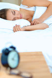 A young woman putting her alarm clock off in the morning.  Royalty Free Stock Image