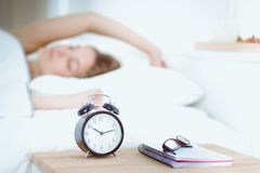 A young woman putting her alarm clock off in the morning. A young woman putting her alarm clock off in the morning Royalty Free Stock Images