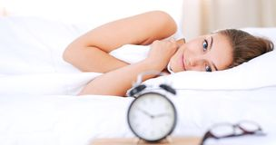A young woman putting her alarm clock off in the morning. Royalty Free Stock Photos