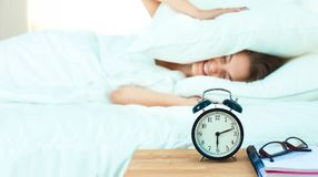 A young woman putting her alarm clock off in the morning.  Royalty Free Stock Photo